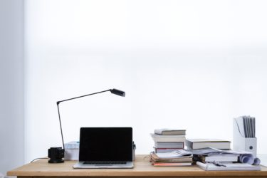 Desk with stack of books and laptop on top